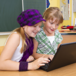 Photo of two primary school girls studying coding in a classroom.